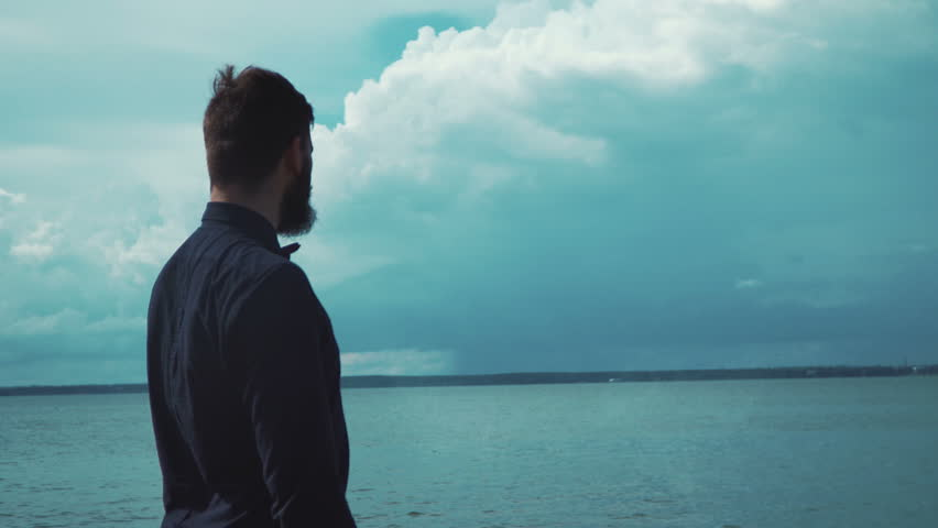 Young stylish man with a beard smokes an electronic cigarette in the background of the sea and clouds epic. Modern fashion vaping #20455090