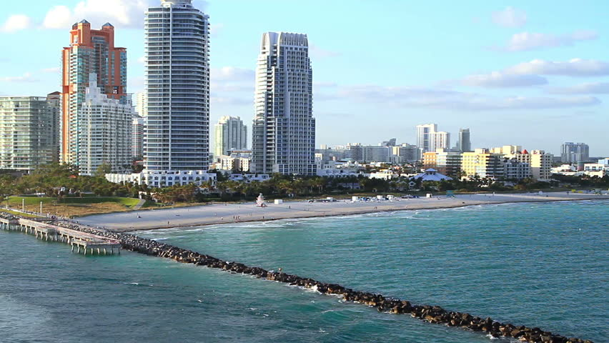 miami beachline with a pier in the water at sunset