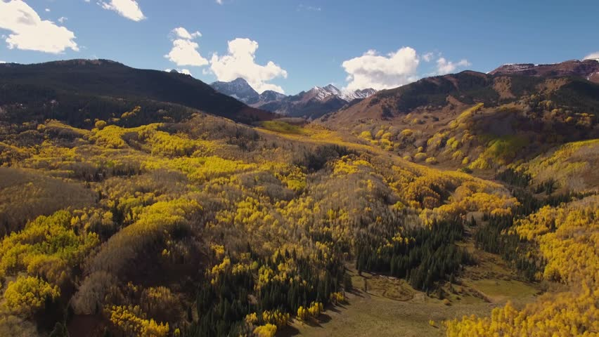 4k Drone/Aerial footage of snow covered Capitol Peak amidst the yellow Fall/Autumn Aspen trees of the Colorado Rocky Mountains.  Filmed near Aspen, Colorado.  USA