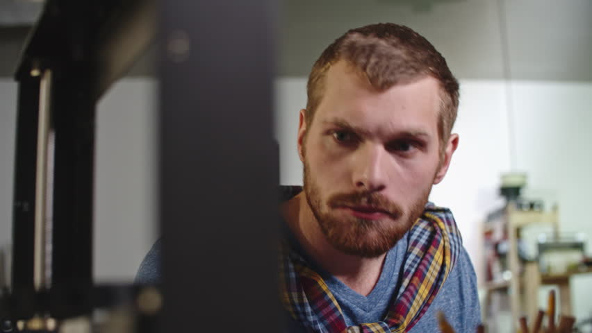 Pan of serious engineer with beard looking at 3d printing machine, then typing something on computer | Shutterstock HD Video #20481991