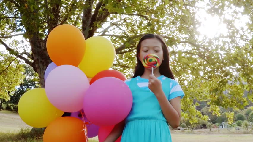 Portrait of smiling girl holding balloons and lollypop in the park on a sunny day | Shutterstock HD Video #20485906