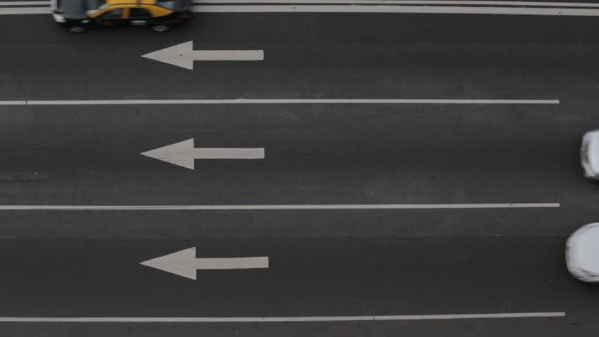 Close up of road, asphalt, white arrow signs indicating direction, way, of the highway. Urban traffic flow, pulse.