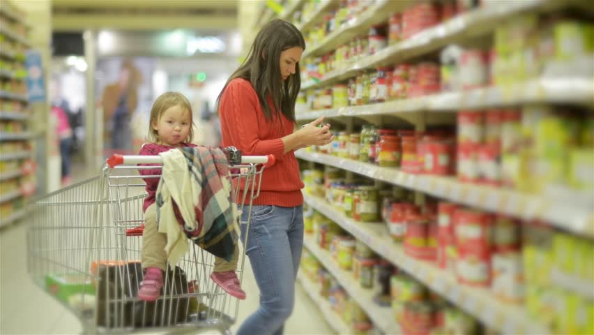 Young Mother and child walks along wholesale shelves and taking goods in shop trolley, woman stands near the supermarket shelf and selects the products for her family | Shutterstock HD Video #20534800