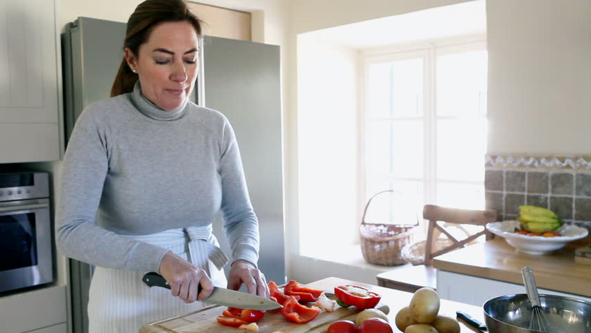 Woman chopping red peppers in the kitchen.