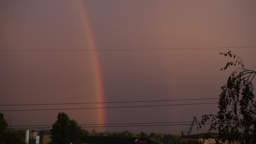 Lightning ad dusk with rainbow in a city on background of grey sky