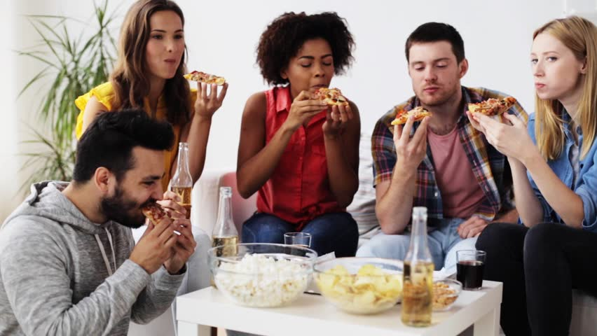 friendship, leisure, fast food and celebration concept - happy friends with drinks and snacks eating pizza at home #20553049