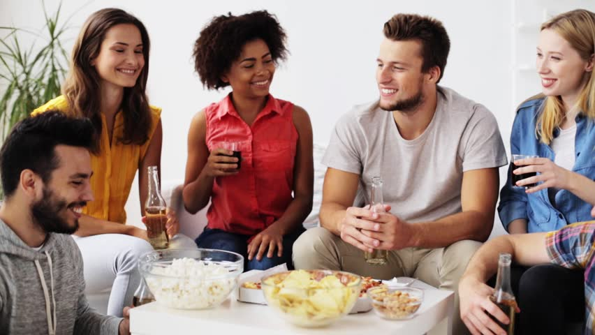 friendship, leisure, fast food, unhealthy eating and celebration concept - happy friends with drinks and snacks clinking bottles at home #20553064