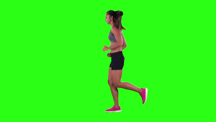 Woman jogging in a medium frontal shot. Green screen. Slow motion