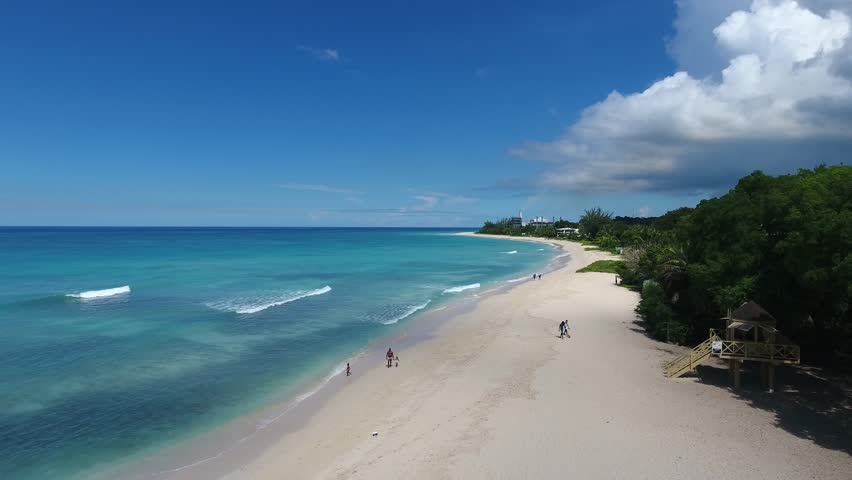 Aerial video of beautiful white sand beaches with lush green trees on a beautiful tropical Beach in the Caribbean
