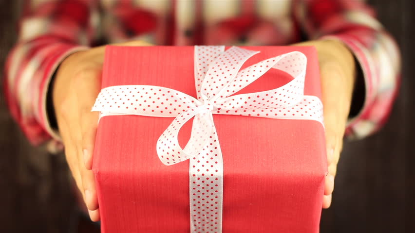 Young man gives a gift on wooden background. Red gift box with white ribbon opening. Congratulate Happy New Year, Merry Christmas, Happy Valentine's Day, presents gifts