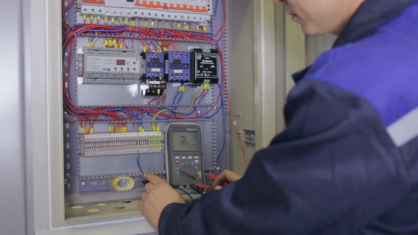 Electrician testing electrical power. Industrial factory electrician testing voltage using multimeter at the electrical shield.