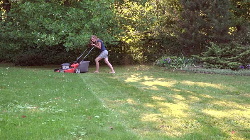 Barefoot blonde woman cut meadow with lawn mower in green garden. video clip. | Shutterstock HD Video #20627962