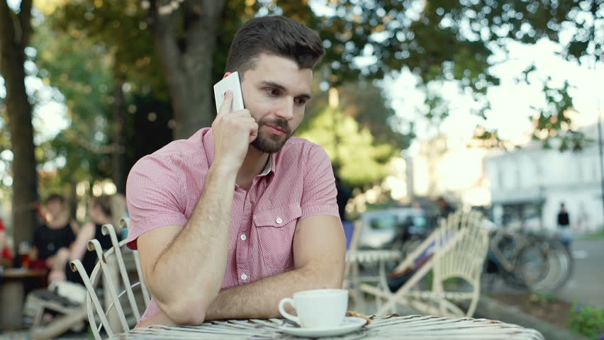 Happy man receives good news while talking on cellphone in the outdoor cafe  | Shutterstock HD Video #20635360