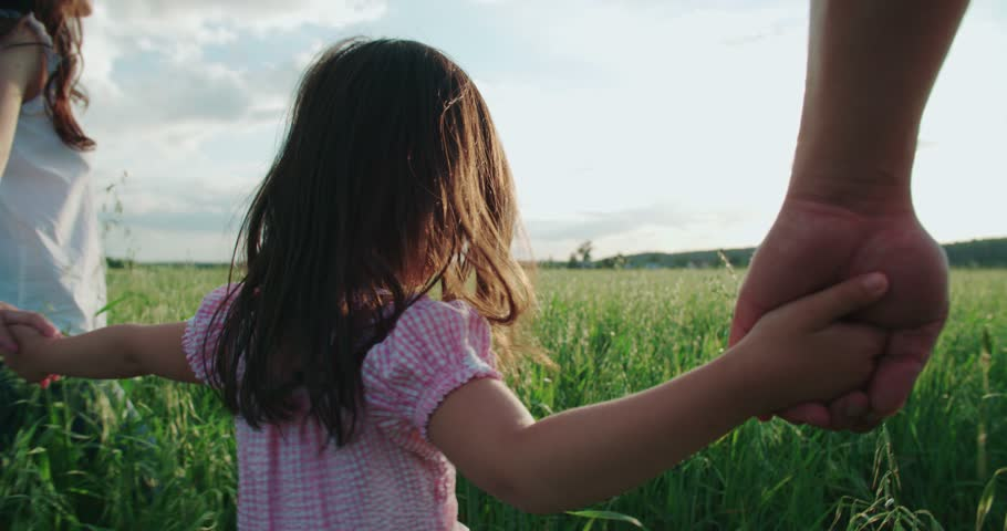 little Asian girl walking on the green field with their parents, holding the hand of his father, slow motion #20643241