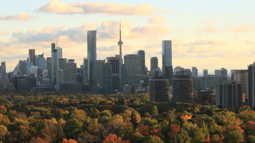 Toronto, Ontario/Canada - October 22, 2016: Autumn Toronto Skyline with downtown and midtown skyscrapers, tree canopy in fall colors lit by setting sun under moving sunset clouds. 4 k time lapse video   Shutterstock HD Video #20656114