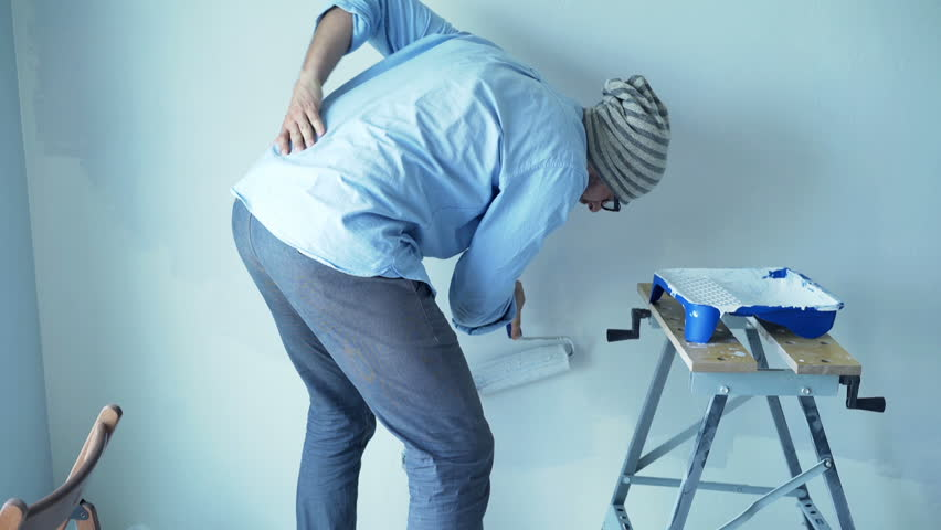 Hipster man having back pain while painting wall at his new home