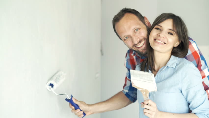 Portrait of happy, young couple painting wall at their new home   Royalty-Free Stock Footage #20665366