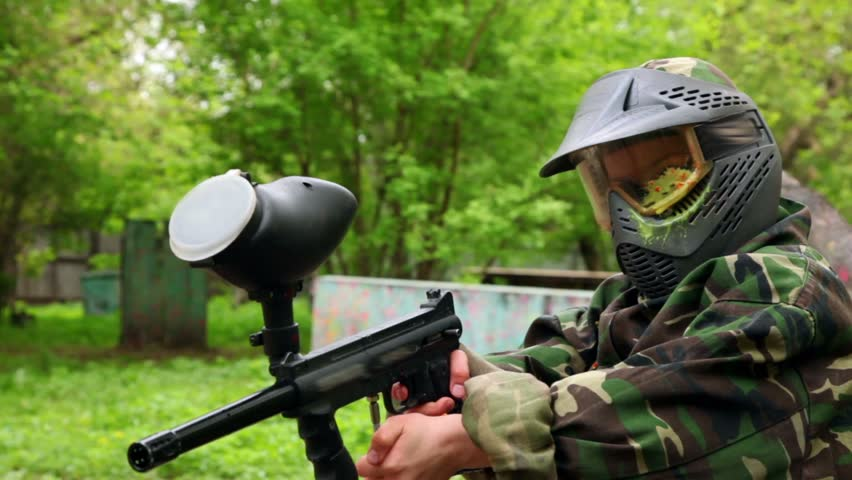 Boy with paint mark on helm holds paintball gun at summer day