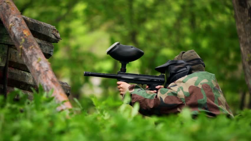 Boy paintball player sits in ambush with gun at background of green leaves