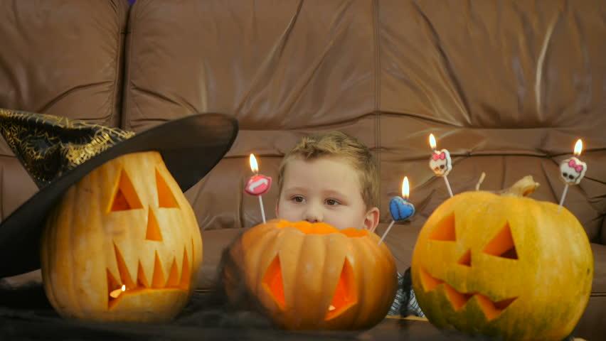 Boy blowsscary candles on pumpkin during Halloween   Shutterstock HD Video #20686261