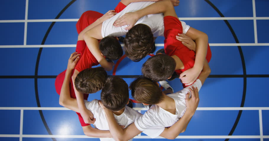 4K Overhead view looking down, young boys standing in a circle on basketball court go into huddle before a game
