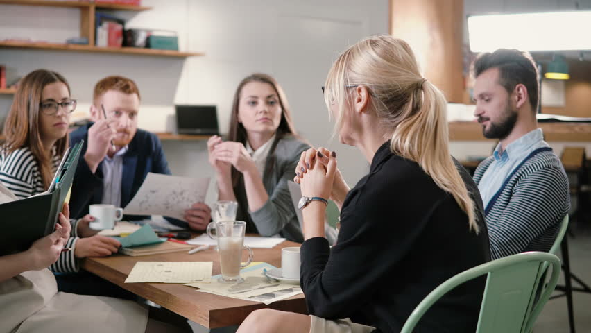 Creative business team at the table in a modern startup office. Female leader explains the details of the project. | Shutterstock HD Video #20697787