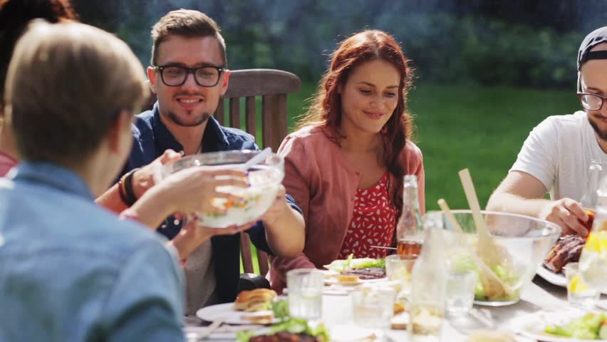 Leisure, holidays, eating, people and food concept - happy friends having dinner at summer garden party | Shutterstock HD Video #20705377