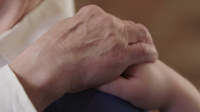 A woman puts a comforting hand on an older elderly woman's shoulder. The older woman puts a hand on the other hand. Shot in 4K UHD. | Shutterstock HD Video #20748082