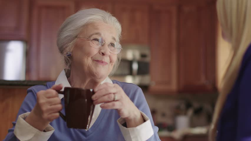 An elderly senior woman enjoys talking with a friend while drinking coffee. Shot in 4K UHD. | Shutterstock HD Video #20748100