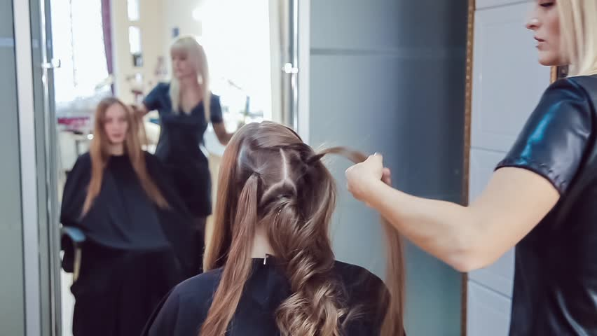 Hair stylist makes professional hairstyle of young woman in beauty studio using curling irons | Shutterstock HD Video #20760256