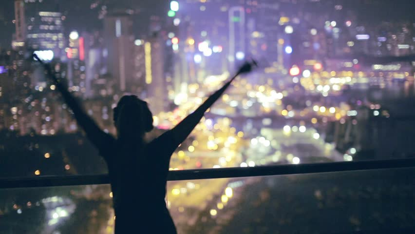 Happy girl  getting excited on the roof with amazing view over city at night. Hong Kong, China.   | Shutterstock HD Video #20788885