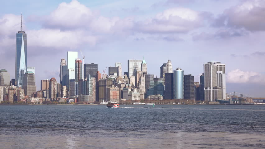 Ship moves through calm waters of Hudson bay below beautiful clouded NYC skyline