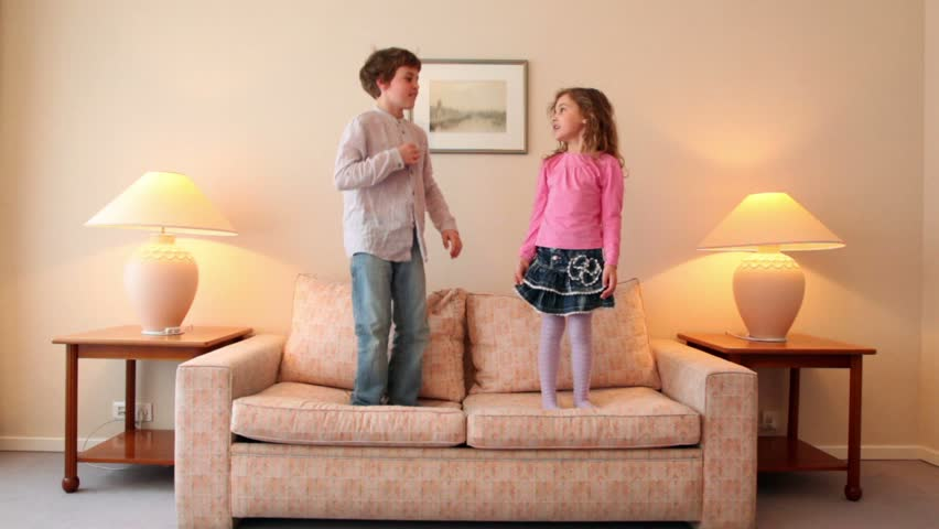 Two kids boy with girl jump on sofa and then run away from room with lamps on each side #2082029