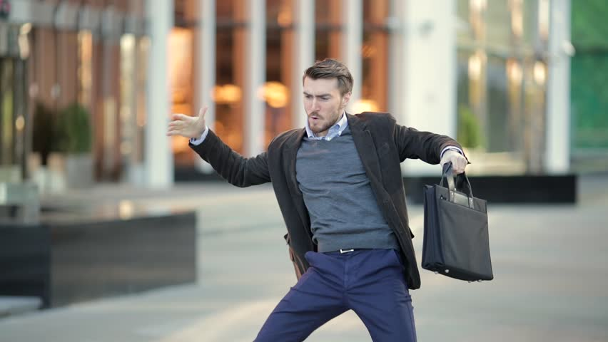 Attractive man with a beard and briefcase dancing in the street | Shutterstock HD Video #20821549