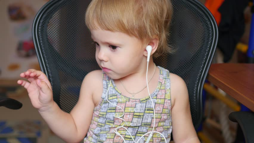 The little child listens to music on smartphone in the headphones in home | Shutterstock HD Video #20825395
