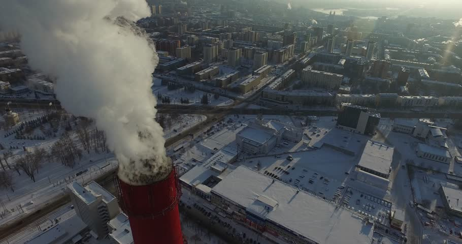Thermal power plant - smoking chimneys various flights of red and white chimney in winter frosty day