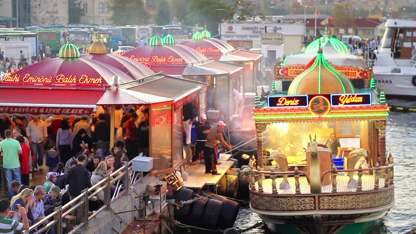 ISTANBUL - OCTOBER 1: Vendors cook and sell fish food on colorful boats at