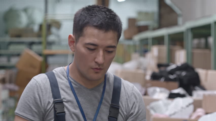 Young Asian warehouse worker pushing cart with cardboard boxes | Shutterstock HD Video #20848192
