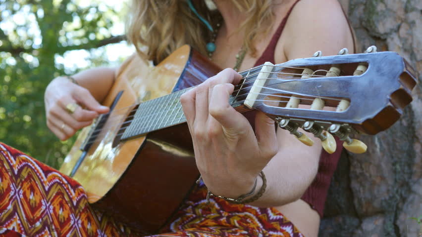 Young blonde hippie woman plays acoustic guitar outdoors. Closeup. Focus on left hand making chord. Shallow depth of field.