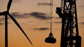 Cargo cranes working in the evening at sundown, discharging a bulk carrier. Windmill is turning around, 4k clip.