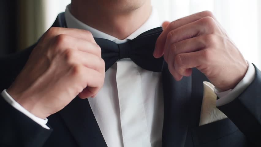 Man adjusts black bow tie closeup slow motion. Male hands correct bowtie on white shirt wear suit prepare for wedding. Gentleman fashion trends fashionable stylish businessman outfit party light image
