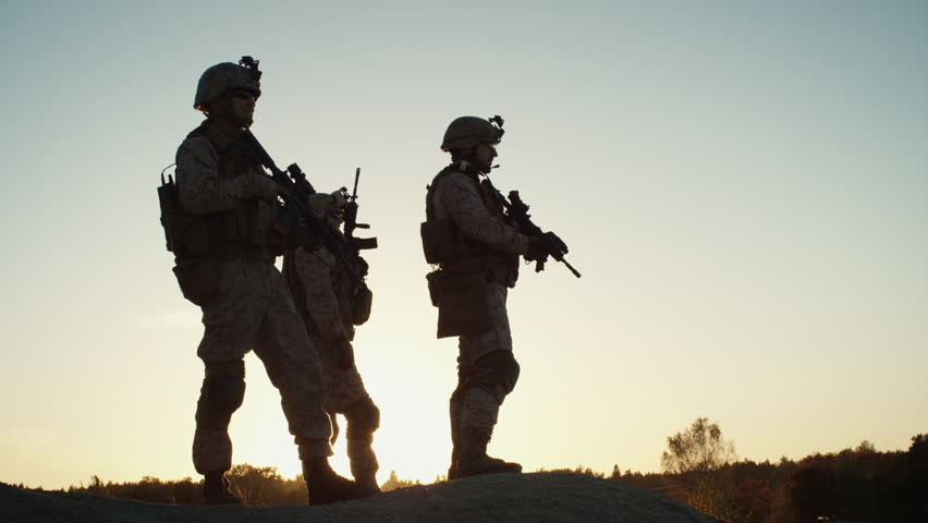 Squad of Three Fully Equipped and Armed Soldiers Standing on Hill in Desert Environment in Sunset Light. Slow Motion. Shot on RED EPIC Cinema Camera in 4K (UHD).