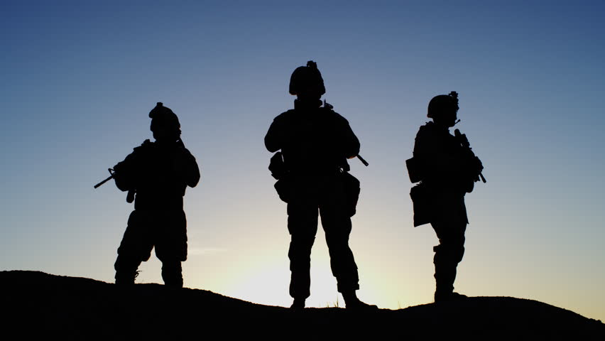 Squad of Three Fully Equipped and Armed Soldiers Standing in Desert Environment in Sunset Light. Slow Motion. Shot on RED EPIC Cinema Camera in 4K (UHD).