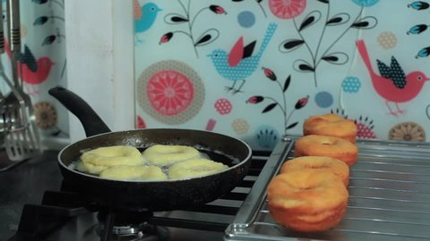 Frying donuts in a kitchen, detail of a kitchen, sweet dessert
