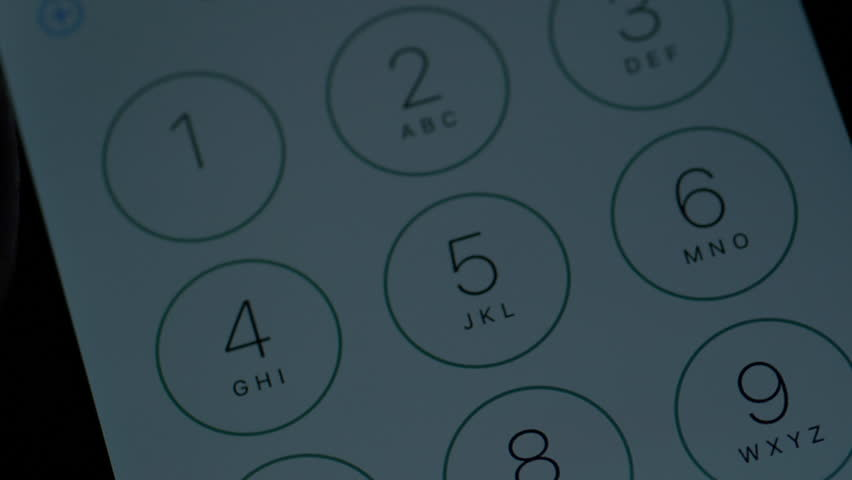 Extreme close up of a cell phone screen dialing 911 emergency call during nightime.