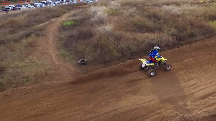 Drone Flies Over the Dirt Road on Which Racing Driver Driving a Sports Atv. Atv Against Quadrocopters. Atv is Clearly Faster and Overtakes on the Highway Drone Bouncing Hills. Atv Rides on the Race