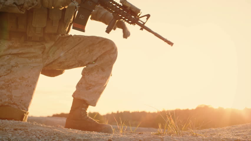 Side view Soldiers Lie Down on the Hill, Aim through the Assault Rifle Scope in Desert Environment in Sunset Light. Slow Motion. Shot on RED EPIC Cinema Camera in 4K (UHD).
