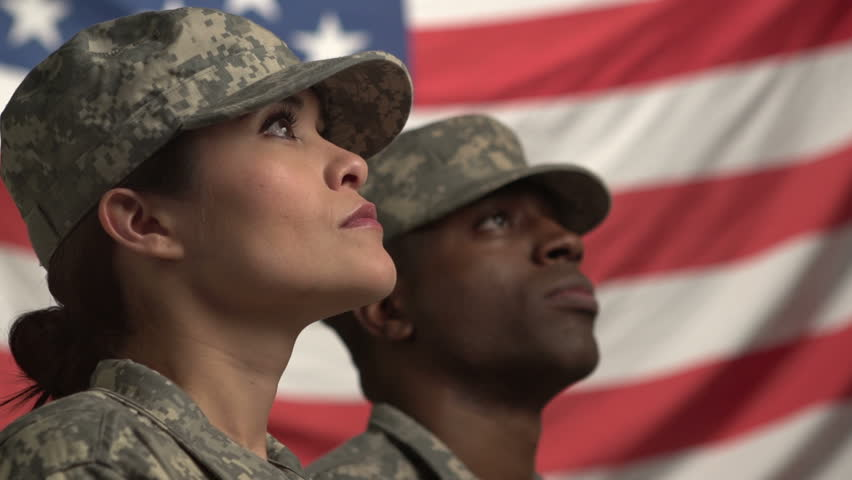 Two U.S. soldiers looking up in front of the flag