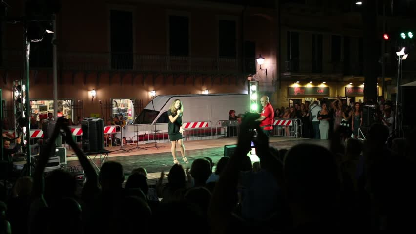 LOANO, ITALY - AUGUST 4, 2016: Woman sings on stage at the audience in the street, the operator shoots the video on camera during the contest of songs performers