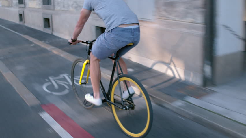 Young hipster man in casual summer cloths riding his fixed gear bike along the bike lane on city street | Shutterstock HD Video #20901706